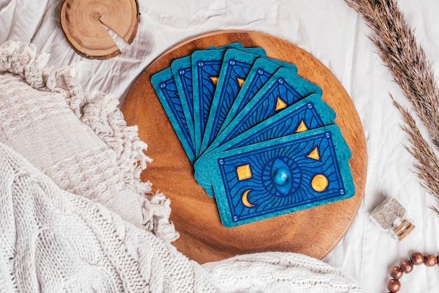 Mazzo di carte dei tarocchi a ventaglio su vassoio di legno su foglio di stoffa bianca con spighette. vista dall'alto. minsk, bielorussia - 27.09.2021