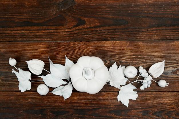 Decor cornice autunnale con foglie bianche e zucca su sfondo piatto in legno marrone scuro.