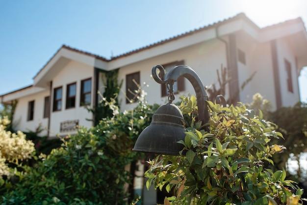 Arredamento dell'edificio. una vecchia campana adorna l'esterno della casa all'ingresso. primo piano. campanello.