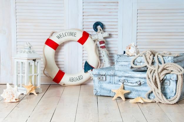 Arredamento nello stile del viaggio in mare, valigie e ancora, salvagente, lanterna.