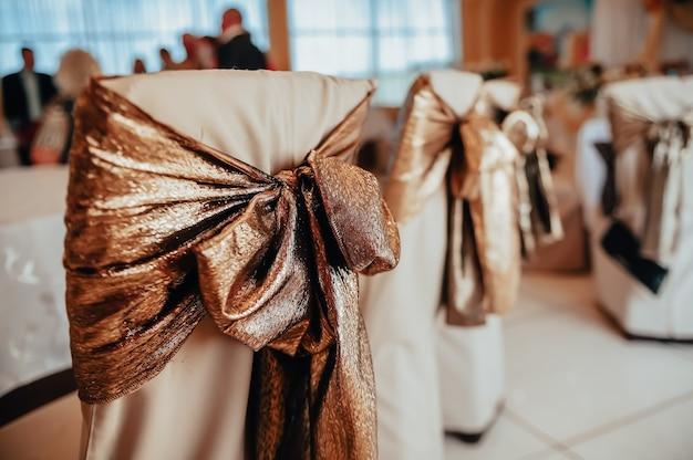 Decorazione di sedie da matrimonio nei toni dell'oro. decorazione di sale per eventi. concetto di matrimonio.