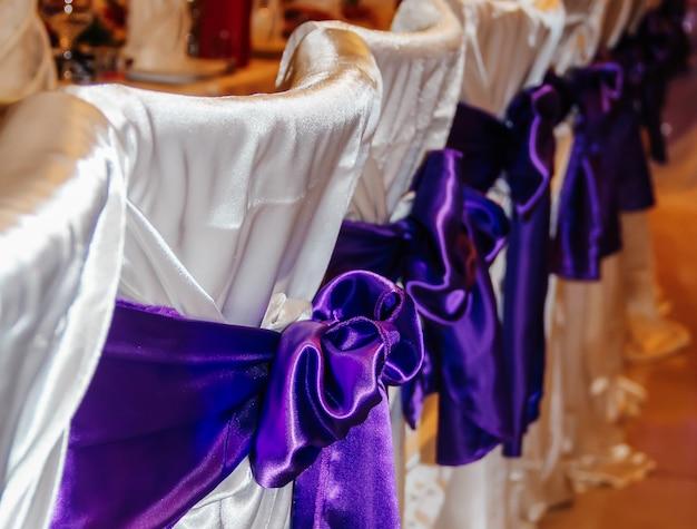 Arredamento di sedie da matrimonio nei toni del viola. decorazione di sale per eventi. concetto di matrimonio.