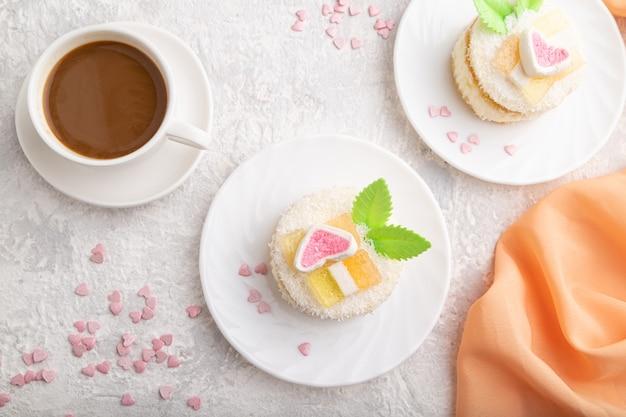 Torta decorata con crema di latte e cocco con tazza di caffè su un cemento grigio
