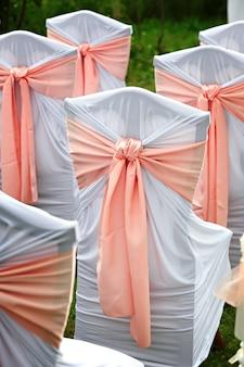 Sedie decorate per gli ospiti di un matrimonio in giardino.