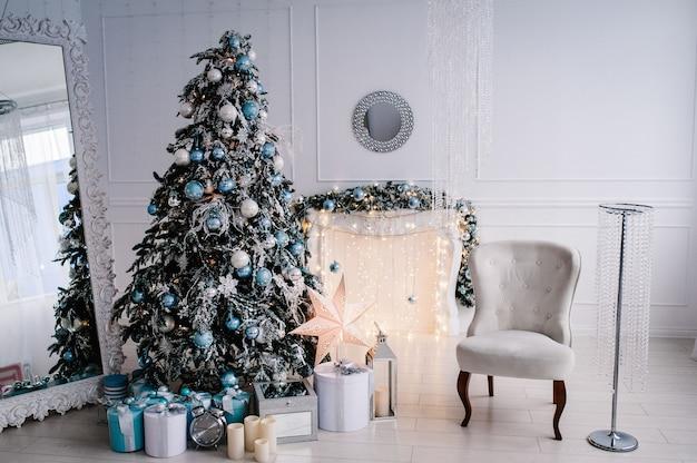 Interno di natale decorato. albero di natale con scatole regalo in una stanza bianca. abete, poltrona, caminetto decorato con ghirlande. decor. buon natale.
