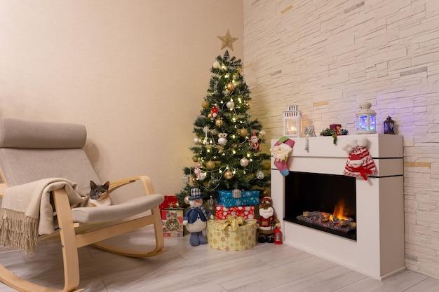 Albero di natale decorato, regali in scatole, un gatto su una sedia vicino al caminetto acceso