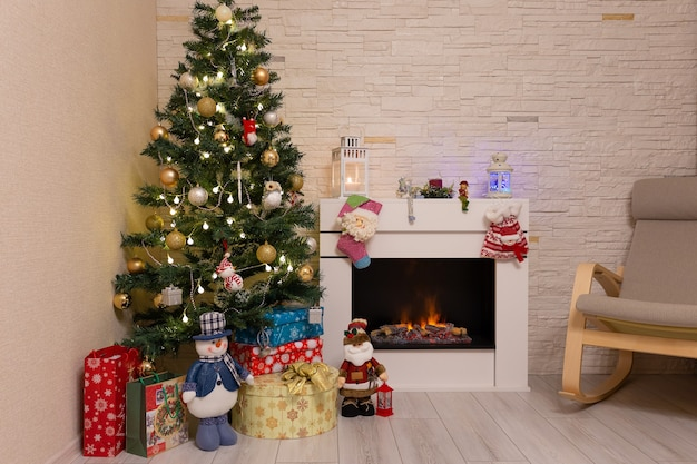 Albero di natale decorato, regali e decorazioni natalizie vicino al camino acceso