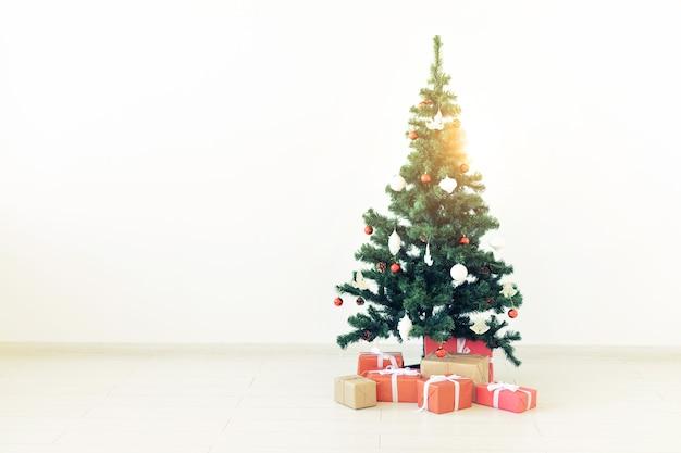 Albero di natale decorato e regali su sfondo bianco con spazio di copia