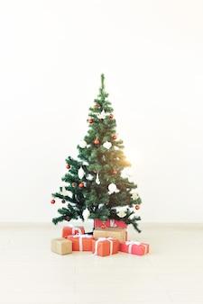 Albero di natale decorato e regali su fondo bianco.