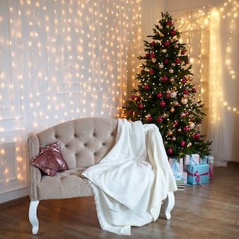 Albero di natale decorato in soggiorno con divano, coperta, ghirlande luminose.