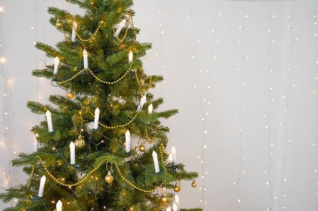 Albero di natale decorato sopra la parete bianca con lo spazio della copia. albero di natale con decorazioni bianche e ghirlanda a forma di candele.