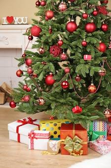 Albero di natale decorato con regali in primo piano della stanza