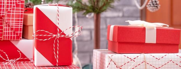 Albero di natale decorato con bellissimi regali rossi e bianchi avvolti a casa con muro di mattoni neri, concetto di design festivo, primo piano.