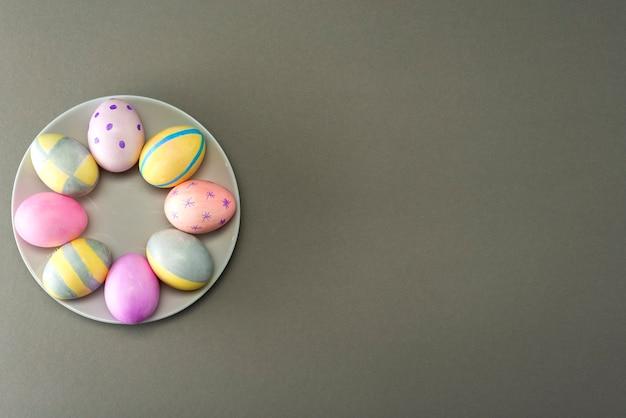Uova di pasqua decorate su un piatto su una superficie grigia con posto per testo