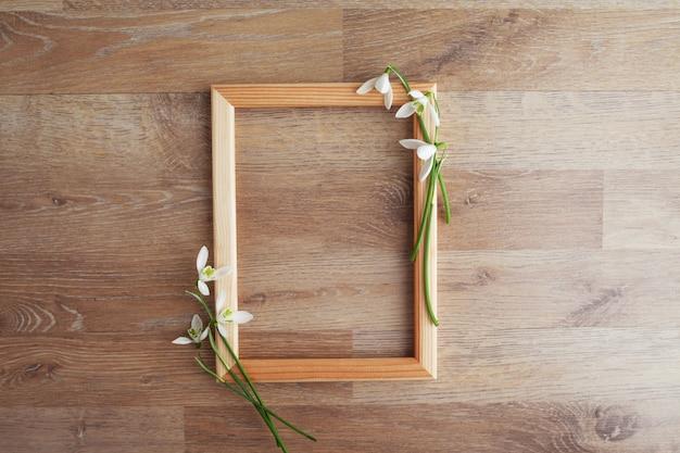 La struttura decorata con i bucaneve fiorisce sulla tavola rustica di legno, fondo di festa per la vostra decorazione. concetto di festa di pasqua e della primavera con lo spazio della copia.