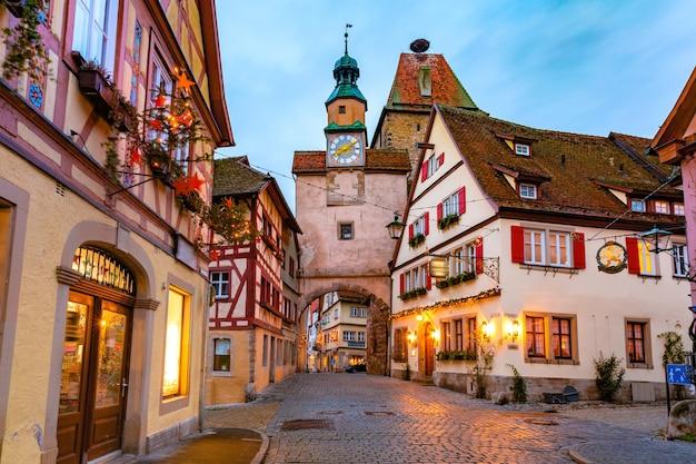 Strada di natale decorata e illuminata con cancello e torre markusturm nel centro storico medievale di rothenburg ob der tauber, baviera, germania meridionale