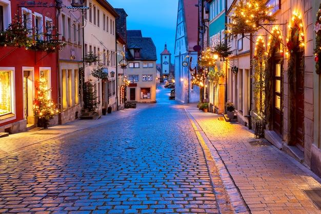 Strada di natale decorata e illuminata con cancello e torre plonlein nel centro storico medievale di rothenburg ob der tauber, baviera, germania meridionale