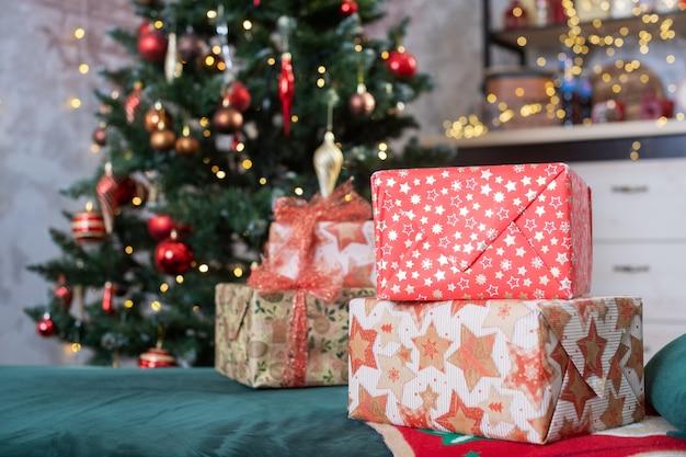 Camera decorata con abete con ornamenti a sfera rossa e dorata, ghirlande leggere, scatole regalo per le vacanze di natale e capodanno
