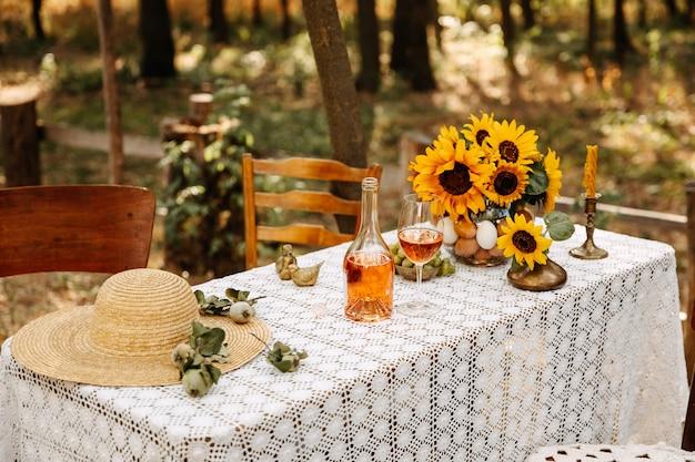 Tavola decorata con tovaglia all'uncinetto, bottiglia di vino, girasoli e cappello di paglia
