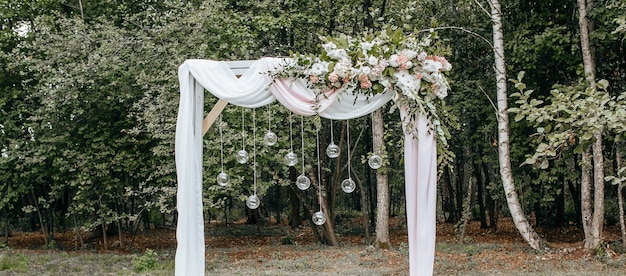 Decorare l'arco con fiori e tessuto per una cerimonia di matrimonio nella natura