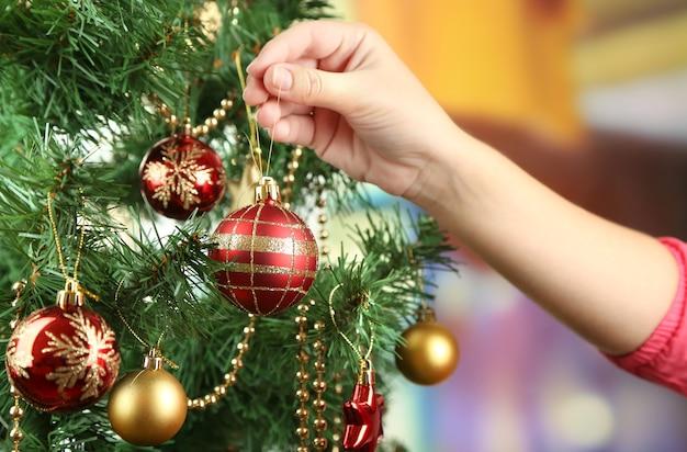 Decorare l'albero di natale su uno sfondo luminoso