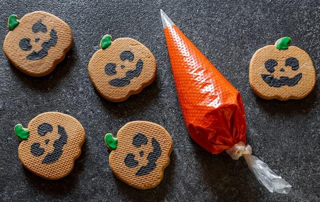 Decorare il pan di zenzero con la glassa di zucca di pan di zenzero di halloween
