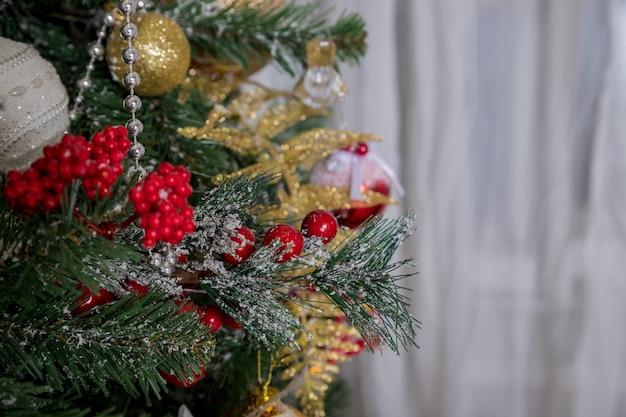 Decorazione. art design. primo piano dell'albero di natale decorato con stella d'oro, bacche di agrifoglio, tinsel. copyspace.baubles che pendono da un albero di natale decorato copyspace