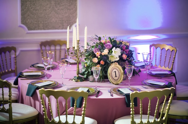 Decorazione della cena festiva con fiori di rosa sul tavolo di nozze all'interno del ristorante. tavola decorata per la celebrazione.