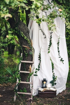 Decorazione per il matrimonio lanterne nere edera ramoscelli canne scale fiori in stoffa bianca su rovere
