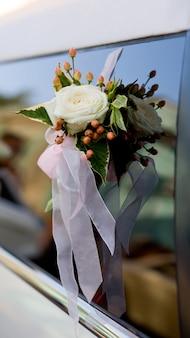 Decorazione di bouquet di rose bianche su auto matrimonio bianco con la riflessione