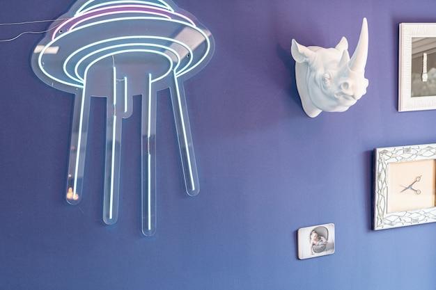 Decorazione con led e testa di rinoceronte bianco appesa a una parete tra quadri in un negozio di barbiere