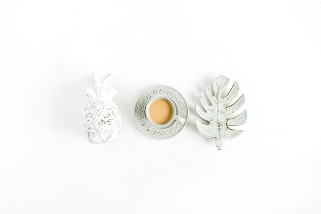 Decorazioni ananas, caffè, foglia di palma monstera su sfondo bianco. disposizione piatta, vista dall'alto