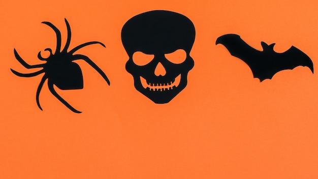 Pipistrello nero decorativo, ragno e palella sullo sfondo di halloween di carta