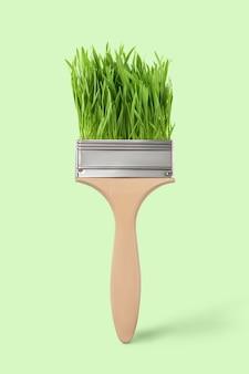 Pennello decorativo con succosa erba fresca su uno sfondo verde chiaro, posto per il testo. pittura concettuale atossica.