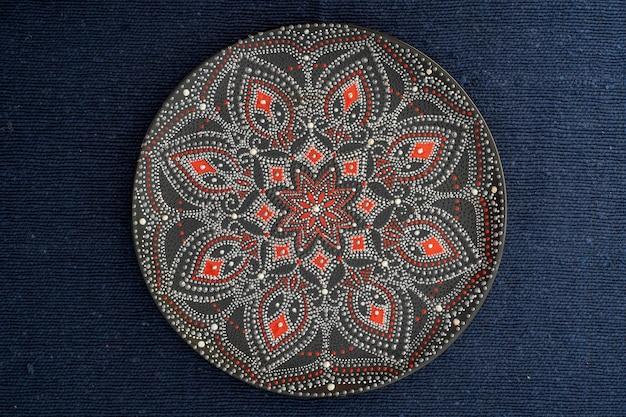 Piatto decorativo in ceramica con colori nero, rosso e dorato, piatto dipinto su sfondo di tessuto, primo piano, vista dall'alto. piatto decorativo in porcellana dipinta con colori acrilici, lavorazione manuale, pittura a punti