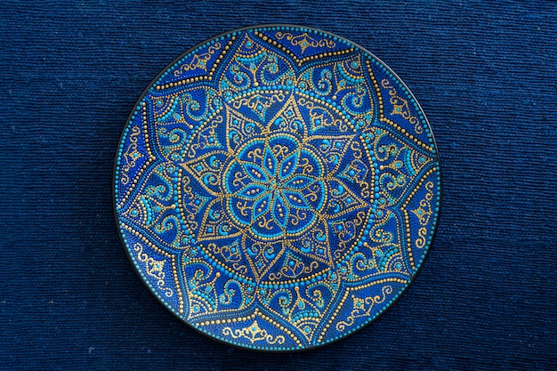 Piatto decorativo in ceramica con colori blu e dorati, piatto dipinto sullo sfondo di tessuto blu, primo piano. piatto decorativo in porcellana dipinto con colori acrilici, lavorazione manuale