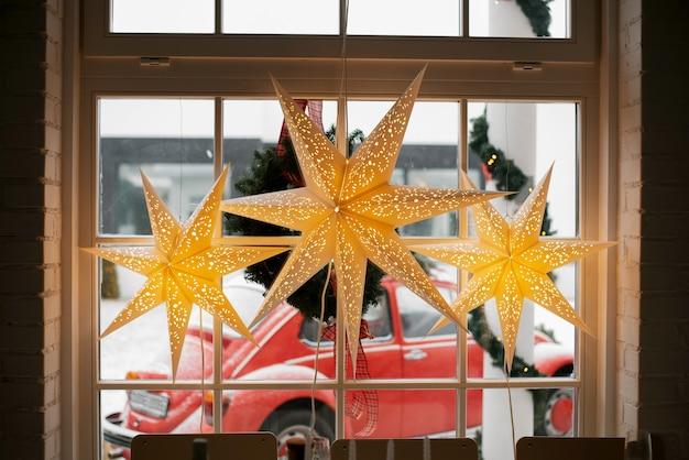 Stelle luminose di natale decorative sulla finestra con vista sul paesaggio invernale