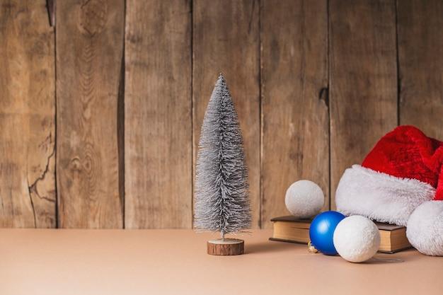 Albero di natale decorativo, decorazioni natalizie e cappello di babbo natale su uno sfondo di legno.