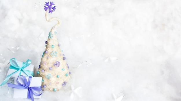 Albero di natale decorativo e regali su uno sfondo innevato. copia spazio. vuoto per congratulazioni per le vacanze invernali