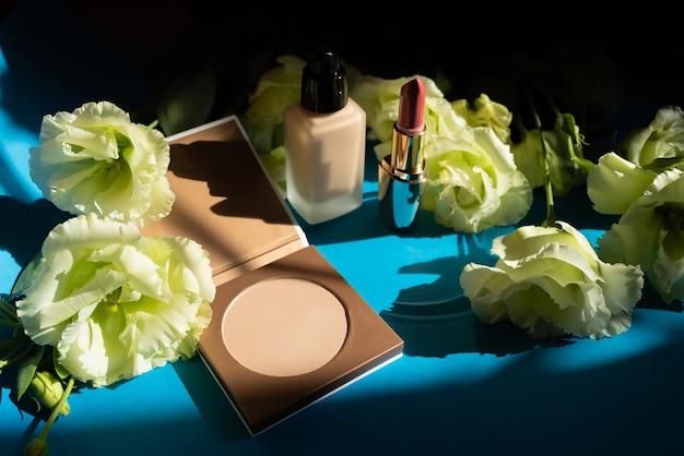 Cosmetici decorativi. polvere, fondotinta e rossetto su sfondo blu. fiori decorativi