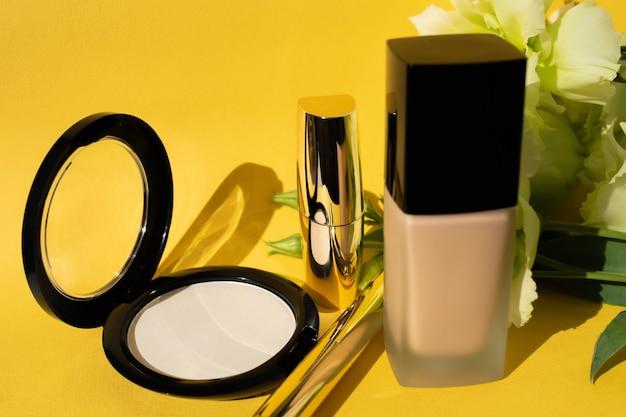 Cosmetici decorativi. polvere, fondotinta e rossetto su sfondo giallo. fiori decorativi