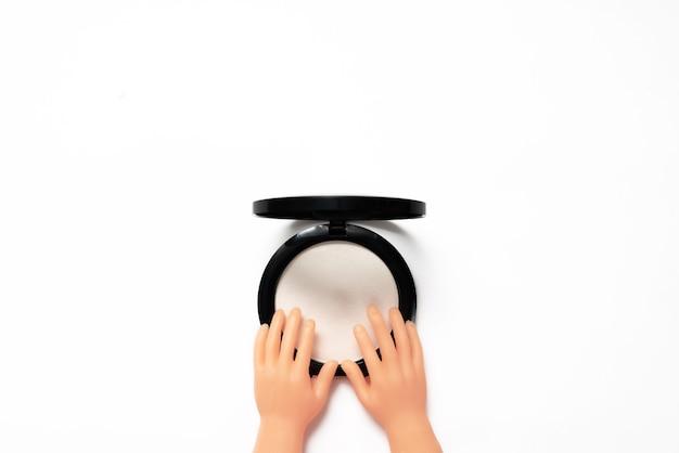 Cosmetici decorativi. piccole mani che toccano la cipria isolata su bianco