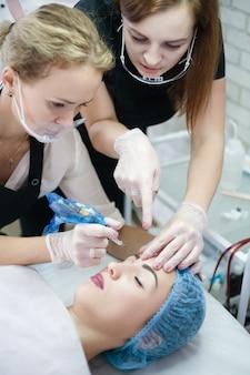 Corsi di cosmetologia decorativa. estetista che insegna a una stagista come utilizzare la macchina per tatuaggi per il microblading delle sopracciglia.
