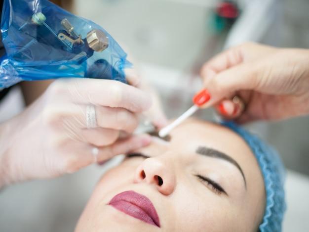 Corsi di cosmetologia decorativa. estetista femminile che utilizza una macchina per tatuaggi per il microblading delle sopracciglia.