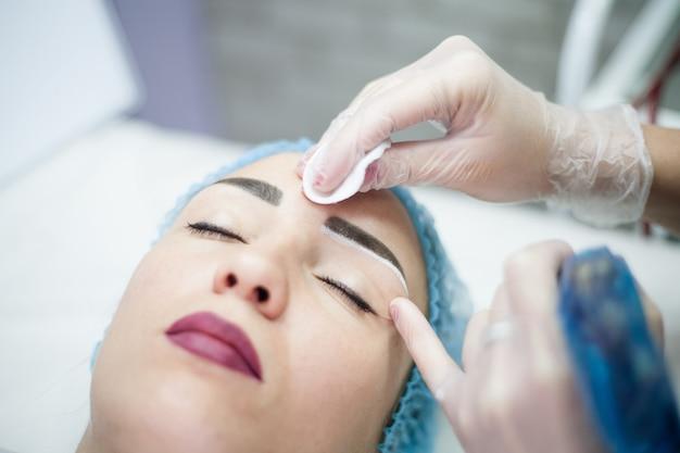 Cosmetologia decorativa. disegno del sopracciglio. ritratto del primo piano del cliente femminile che gode della procedura di bellezza.