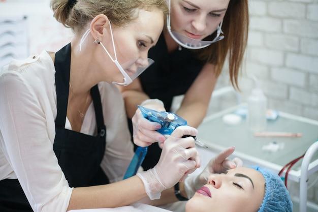 Formazione pratica di cosmetologia decorativa. stagista femminile che utilizza una macchina per tatuaggi per il microblading delle sopracciglia.