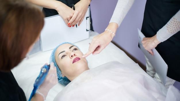 Cosmetologia decorativa. trattamento professionale della pelle. donne che imparano una nuova tecnica di trucco permanente, la colorazione delle labbra.