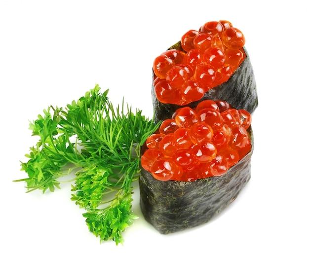 Primo piano decorativo del caviale dei sushi del piatto. su un muro bianco