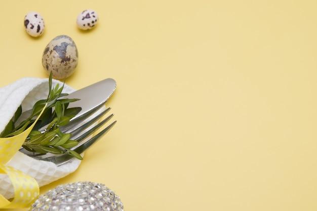 Uovo di pasqua decorativo e posate su uno sfondo giallo con spazio di copia