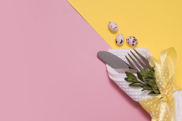 Uovo di pasqua decorativo e posate su uno sfondo giallo-pinnk